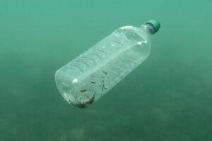 Water bottle filled with debris floating underwater.